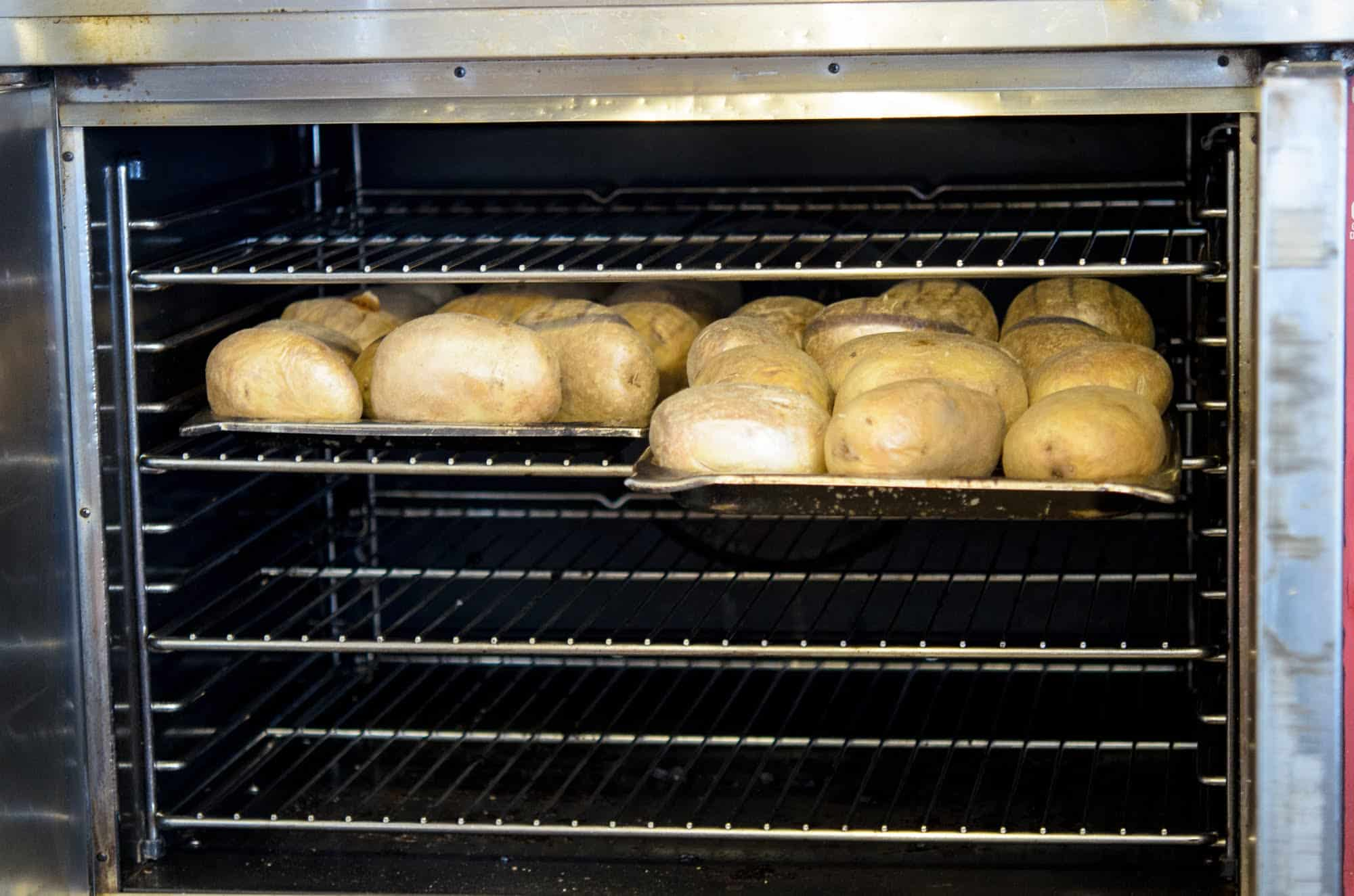 Potatoes go into the oven in the Baked Potato Shop